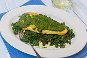 foto of sauteed  - Sauteed fish topped with pesto on a bed of sauteed kale - JPG