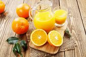 stock photo of jug  - Orange juice in the glass jug on the wooden table - JPG