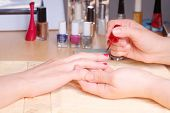 picture of nail salon  - Manicurist doing manicure client painting nails with red nail polish in salon on yellow towel  - JPG