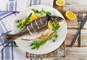 stock photo of plate fish food  - Fried sea bream fish on plate with fresh salad and lemon - JPG