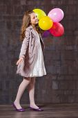 foto of ten years old  - Ten year old caucasian girl with long hair posing in the studio with balloons - JPG
