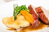 picture of scallops  - Sliced pork tenderloin with scallopped potatoes garnished with rosemary and vegetables - JPG