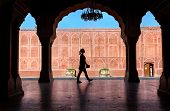 picture of rajasthani  - Woman silhouette with guidebook walking in the City Palace museum Jaipur Rajasthan India - JPG