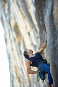 stock photo of climbing wall  - rock climber climbs on a rocky wall - JPG