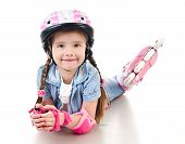 stock photo of roller-skating  - Cute smiling little girl in pink roller skates and protective gear isolated on a white - JPG
