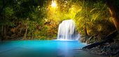 Постер, плакат: Exotic background of beautiful jungle forest with majestic waterfall falling into blue water lake an