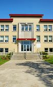 pic of school building  - Brick building entrance with cement walkway and sky - JPG