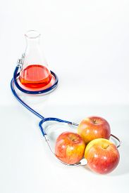 stock photo of modification  - Stethoscope with apple analytical Genetic Modification gm food - JPG