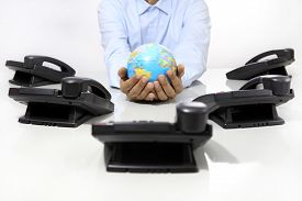 picture of globe  - hands globe with office phones on desk global international support concept - JPG