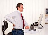 stock photo of spinal column  - Young man in office with computer and back pain - JPG