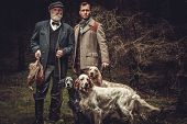 Two hunters with dogs and shotguns in a traditional shooting clothing. poster