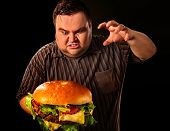 Diet failure of fat man eating fast food hamberger. Aggressive overweight person who spoiled healthy poster