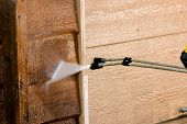 image of pressure-wash  - The side of a garage being pressure washed  - JPG