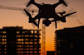 Silhouette of Unmanned Aircraft System (UAV) Quadcopter Drone In The Air Over Buildings Under Constr poster