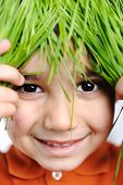 Cute happy kid with green natural grass hair on head