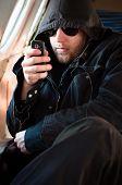 Hombre encapuchado mirando su celular