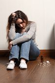 image of teenage girl  - Teenage girl sitting on the floor at home looking scared and frightened - JPG
