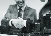 business, cooperation, partnership and people concept - two businessmen shaking hands at office over poster