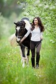 Young woman and pinto horse in apple garden. Horse and beautiful lady walking outdoor. Horse rider. poster