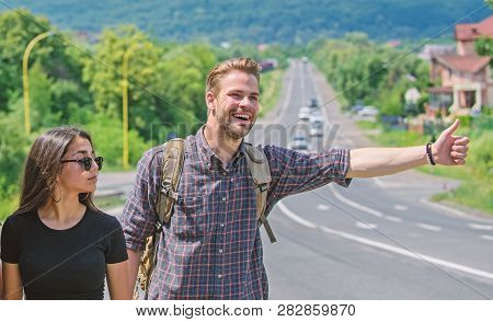 poster of Couple Travelers Man And Girl Hitchhiking At Edge Road Nature Background. Travel By Autostop. Couple