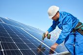 Man Worker In Blue Suit And Protective Helmet Installing Solar Photovoltaic Panel System Using Screw poster