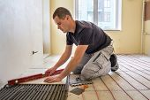 Young Worker Tiler Installing Ceramic Tiles Using Lever On Cement Floor With Heating Red Electrical  poster