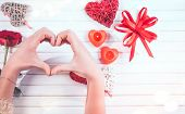 Making heart shape with hands. Woman Hands making heart, gift box with red bow, candles, gift and re poster