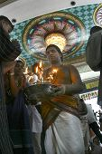 KUALA LUMPUR, MALAYSIA - OCTOBER 2011 Hindus receive blessings from a priest holding an oil lamp dur