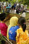 KUALA LUMPUR, MALAYSIA - NOVEMBER 2011 3 siblings looking at the slaughter process during the Hari R