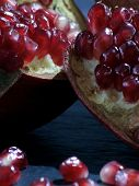 Horizontal Close-up Of Red Slices. Juicy Pomegranate Fruit On A Dark Blue Background. Health Food Fo poster