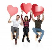 three casual people with hands in the air celebrating love by holding big red hearts for valentines poster