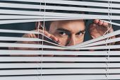 Young Man Spying And Looking At Camera Through Blinds poster
