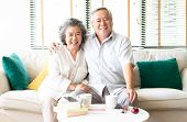 Portrait Of A Happy Asian Senior Couple Relaxing At Home On The Sofa With The Wife Hugging Her Husba poster