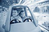 Children In Toy Automobile In Supermarket