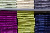 Shelves With Towels Stacks In Shop. Piles Of Multicolored Towels On The Shelves. Stack Of Towels In  poster