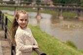 Girl Child Tourist Enjoy Sightseeing While Walks. Kid Girl With Long Hair Walks Near Riverside, Rive poster