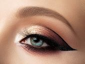 Close Up Of Beautiful Woman Eye With Multicolored Fashion Makeup And Modern Eyeliner Wing. Studio Sh poster