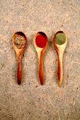Especias secas en cucharas de madera.