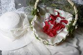 Bridal Hat Beside A Basket Of Rose Petals poster