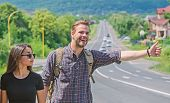 Couple Travelers Man And Girl Hitchhiking At Edge Road Nature Background. Travel By Autostop. Couple poster