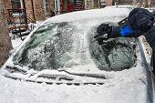 Montreal, Canada - 7 February 2019: Man Cleaning Car Windshield From Snow Ice With Scraper Tool. poster
