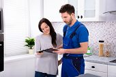 Close-up Of Young Male Plumber Showing Invoice To Woman In Kitchen poster