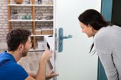 Smiling Woman Looking At Technician Fixing The Door Lock With Screwdriver At Home poster