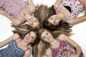 Overhead view of four teenage girls lying on white floor.