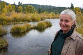 image of beautiful senior woman  - senior woman standing on bank of river in fall - JPG