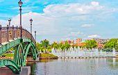 Big Fountain And Green Bridge In Summer Park