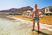 A Man In Swimming Trunks Stands On The Shore Of The Dead Sea In Israel Against The Background Of The