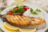 Peixe com arroz cozido e salada no prato