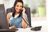 stock photo of hindu  - attractive young indian receptionist talking on the phone - JPG