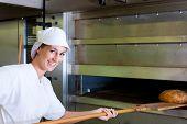 Female baker baking fresh bread in the bakehouse